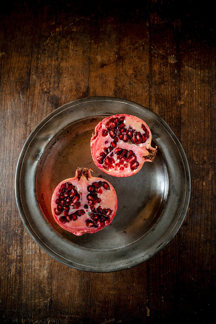 Pomegranate cut in half on a metal plate