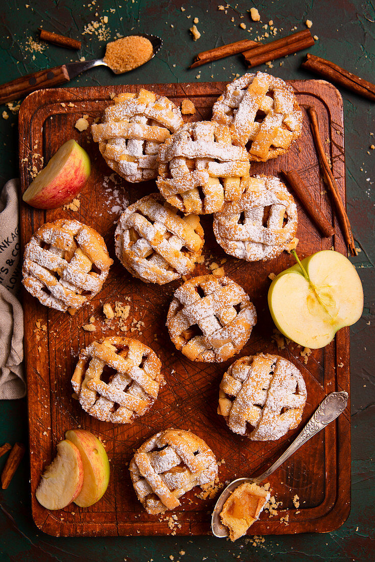 Mini apple pies with cinnamon and sugar powder on a wooden board