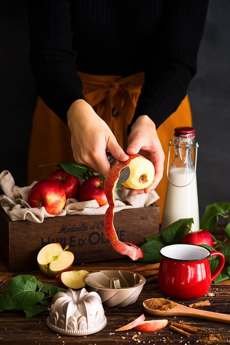 Woman peeling an apple autumn scenery with apples and cinnamon