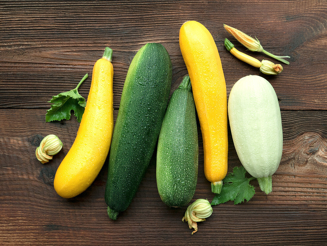Various fresh yellow, green and white zucchini on a wooden background