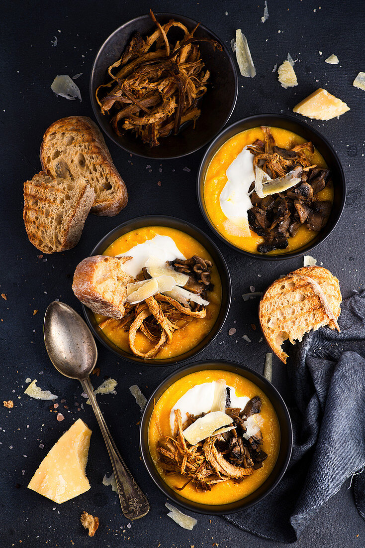 Carrot pumpkin cream soup with pulled pork, thick cream croutons and Parmesan cheese