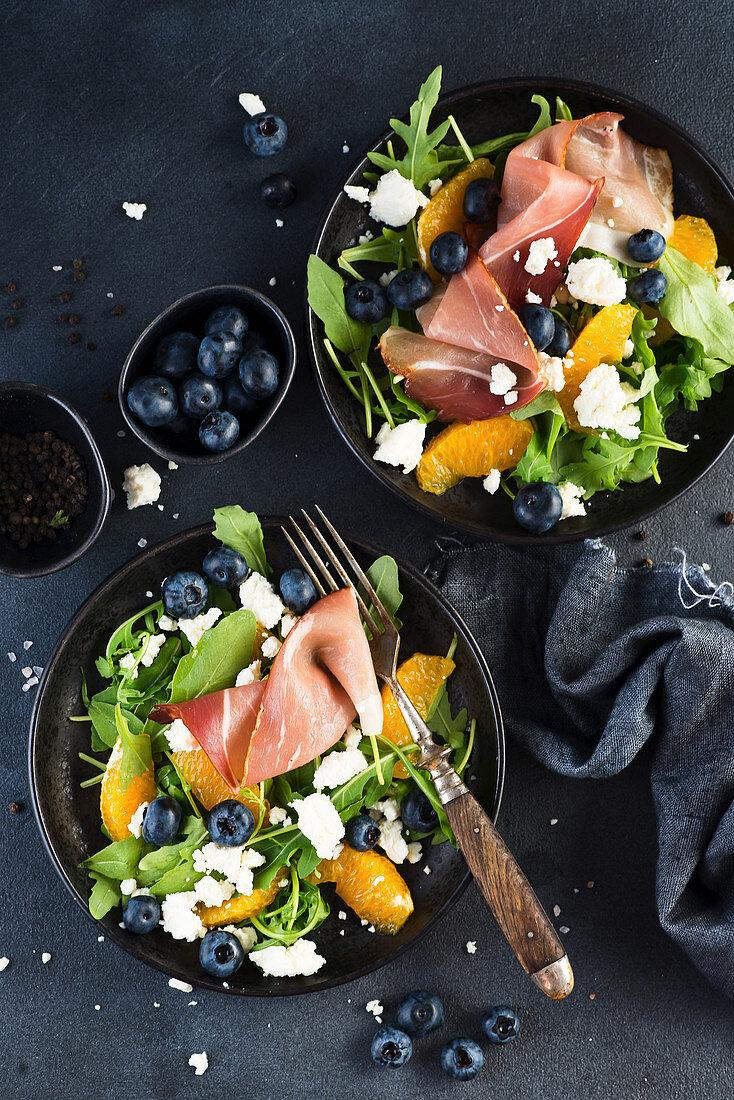 Salad with arugula, blueberries, feta cheese, Parma ham and orange