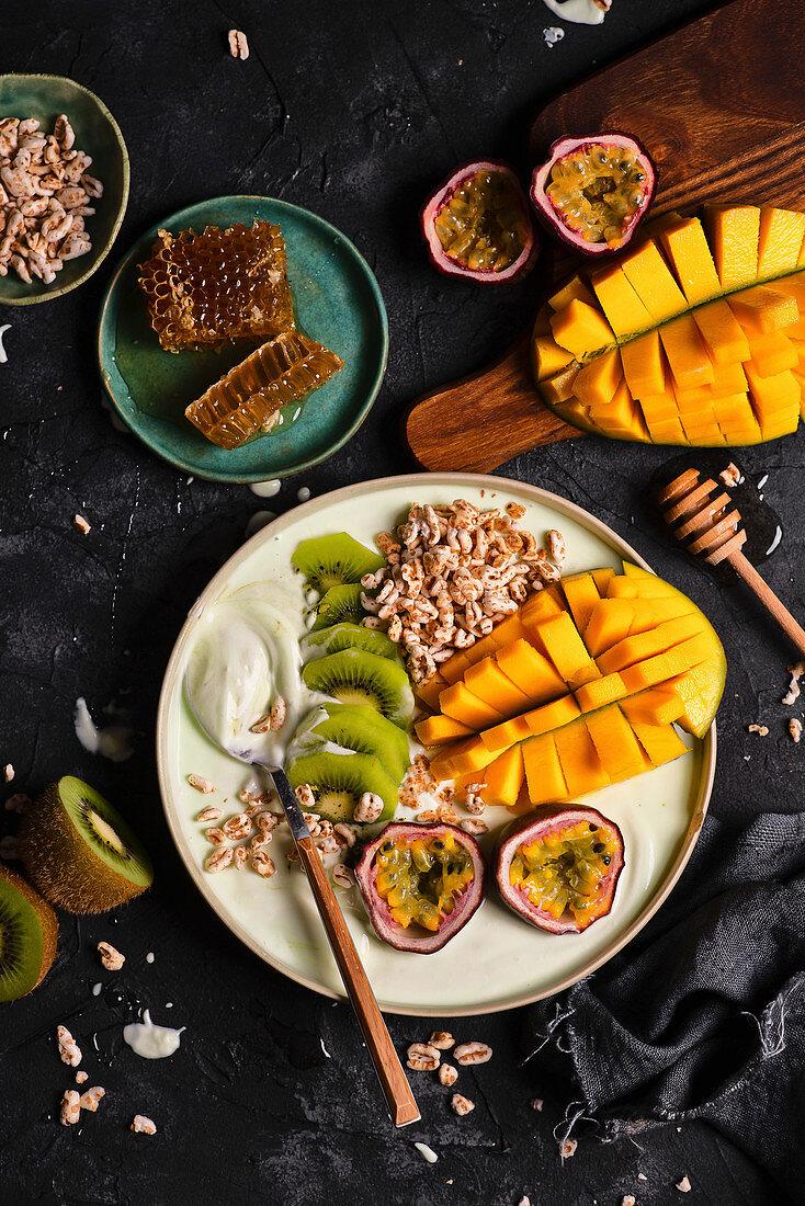 Smoothie bowl with matcha, mango, passion fruit, kiwi and expanded spelled