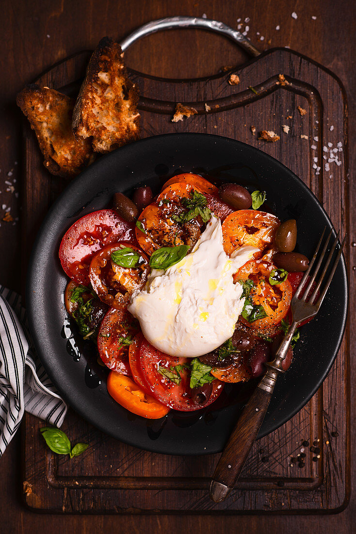 Red and yellow tomato salad with burrata, basil and balsamic vinegar
