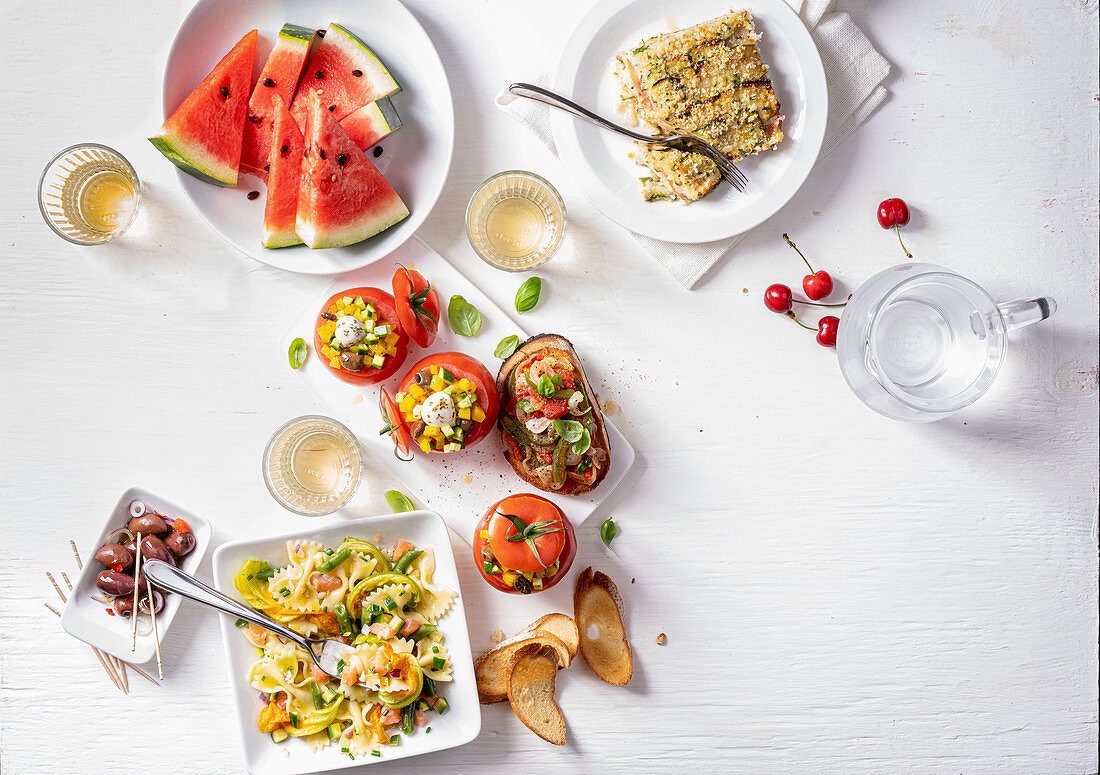 Various summer dishes on a white surface