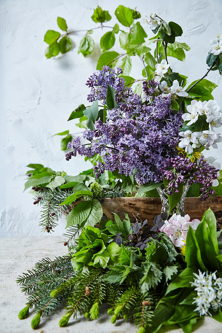 A spring flower arrangement with lilac, fruit blossom, leaves and needles