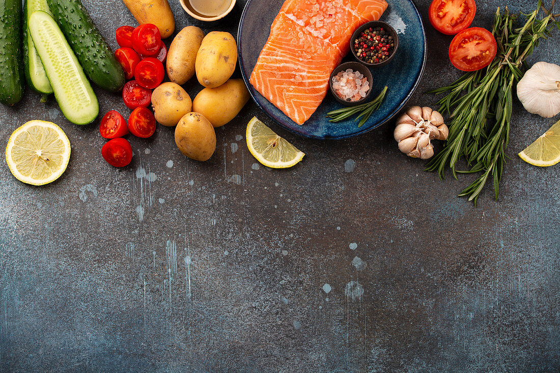 Raw salmon fish fillet, fresh vegetables, herbs - ingredients for cooking healthy meal