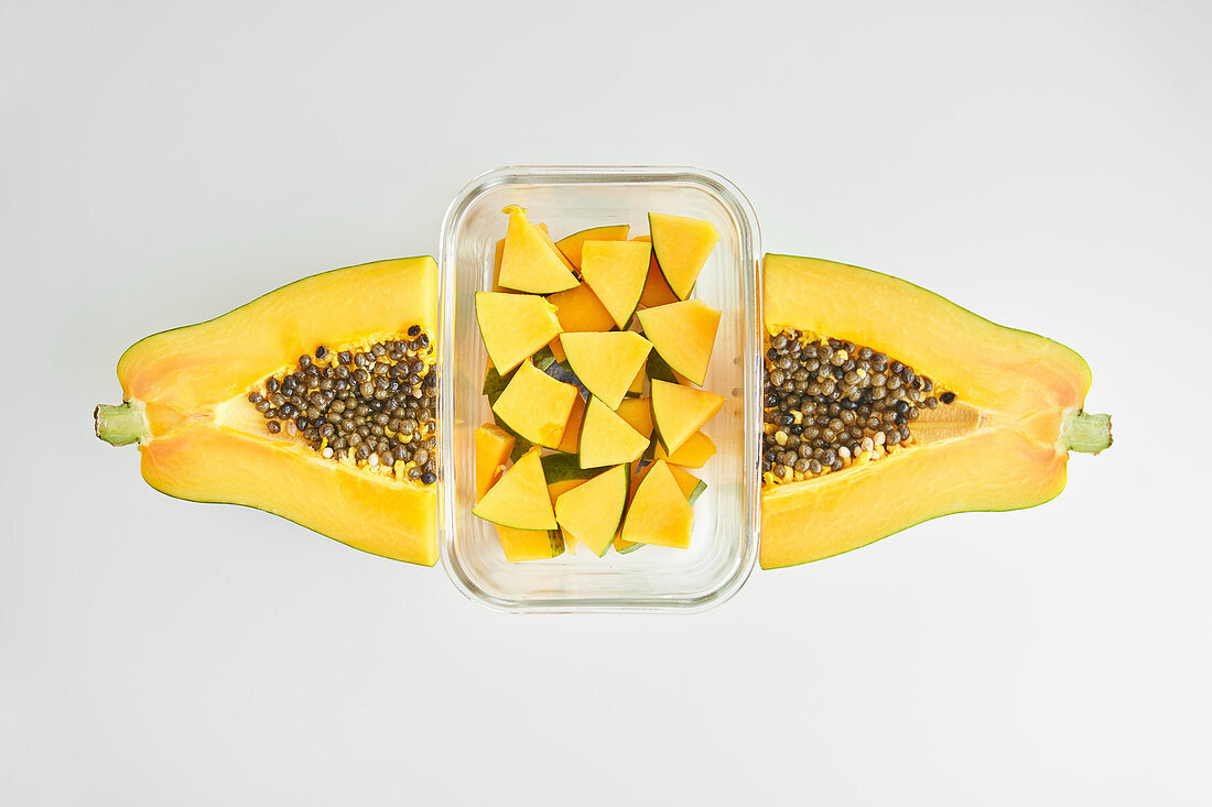Papaya and glass container with pieces of fresh fruit placed on white background