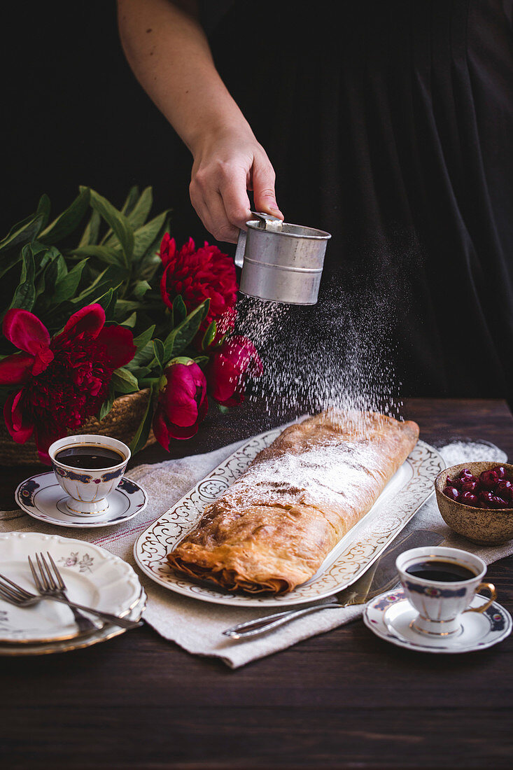 Woman dusting sour cherries strudel with powdered sugar