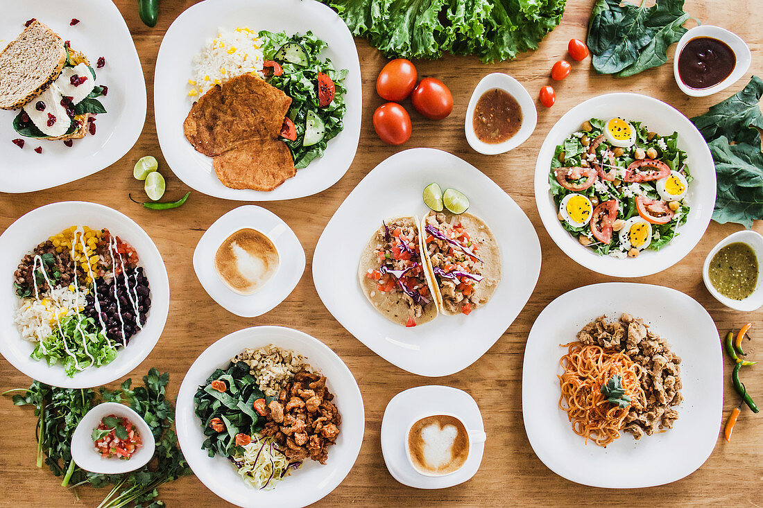 Bowls and plates of delicious healthy dishes with vegetables and meat