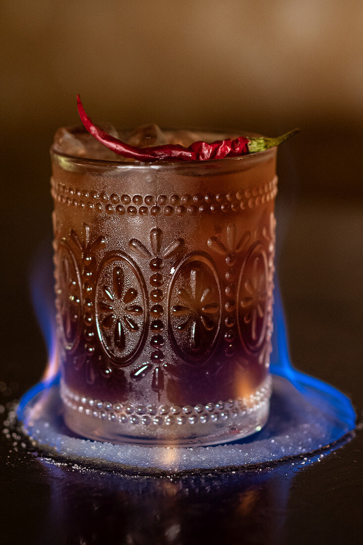Flaming alcohol cocktail with ice cubes garnished with spicy chili in bar