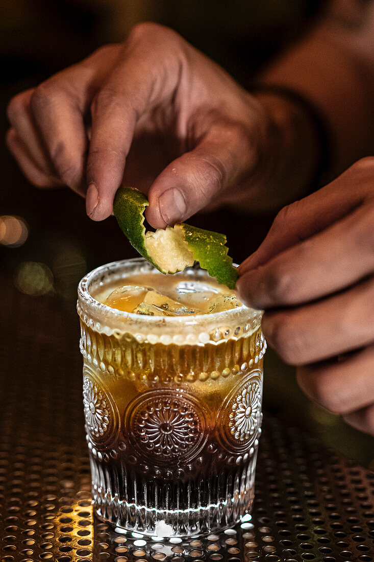 Unrecognizable barman putting curly lime peel on cup with alcohol drink during work in pub