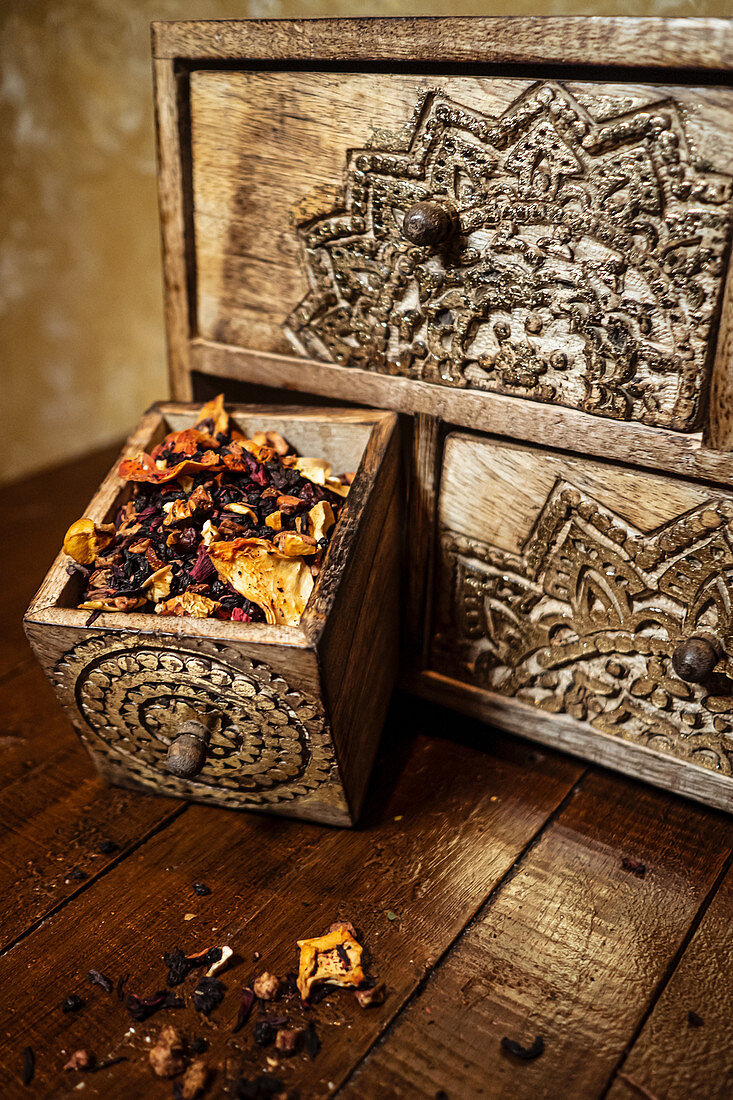 High angle of weathered old drawer with dried flower petals and herbs placed on table