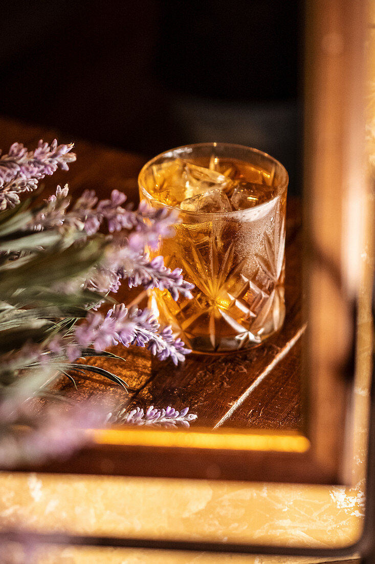 Old fashioned glass with alcohol drink placed on table with lavender flowers and reflected in mirror