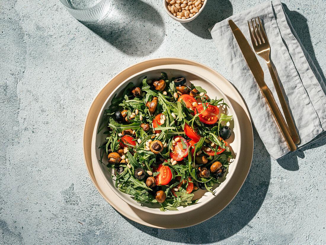 Salad with arugula, mini champignons, cherry tomatoes, black olives, pine nuts