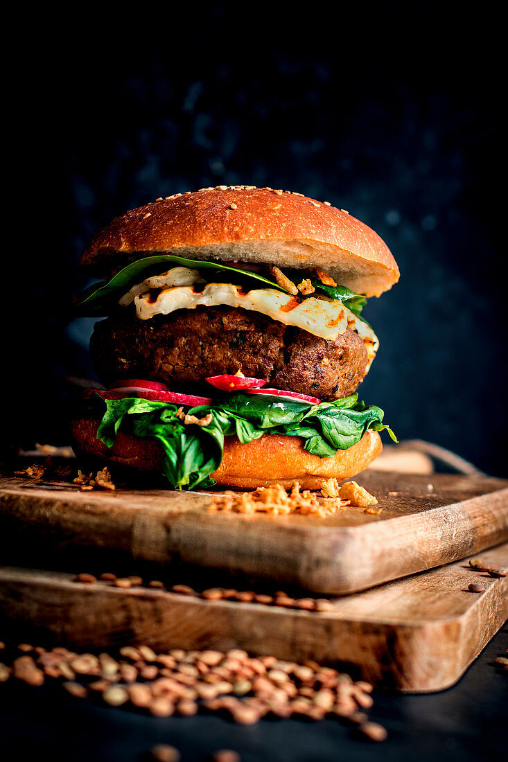 Lentils vegan hamburgers placed on wooden board on dark background