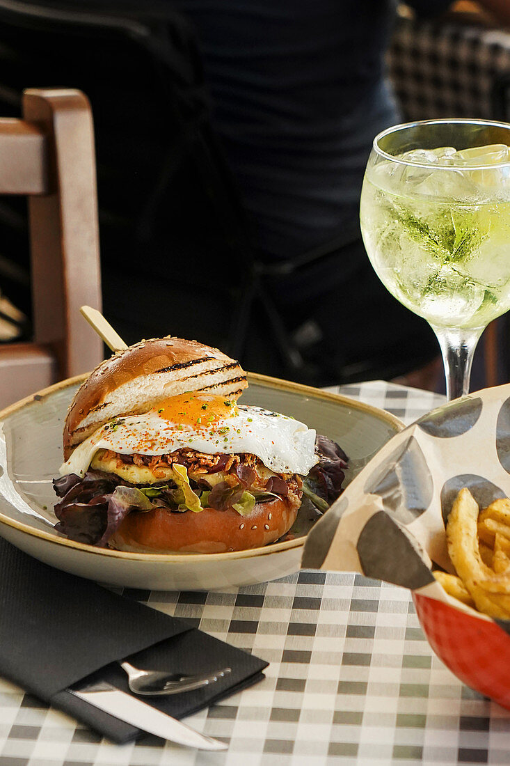 Juicy burger with fried egg and fries on table with glass of cool lime cocktail in cafe