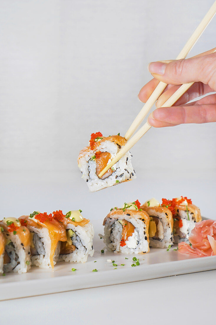 Holding sushi with chopsticks above white wooden table