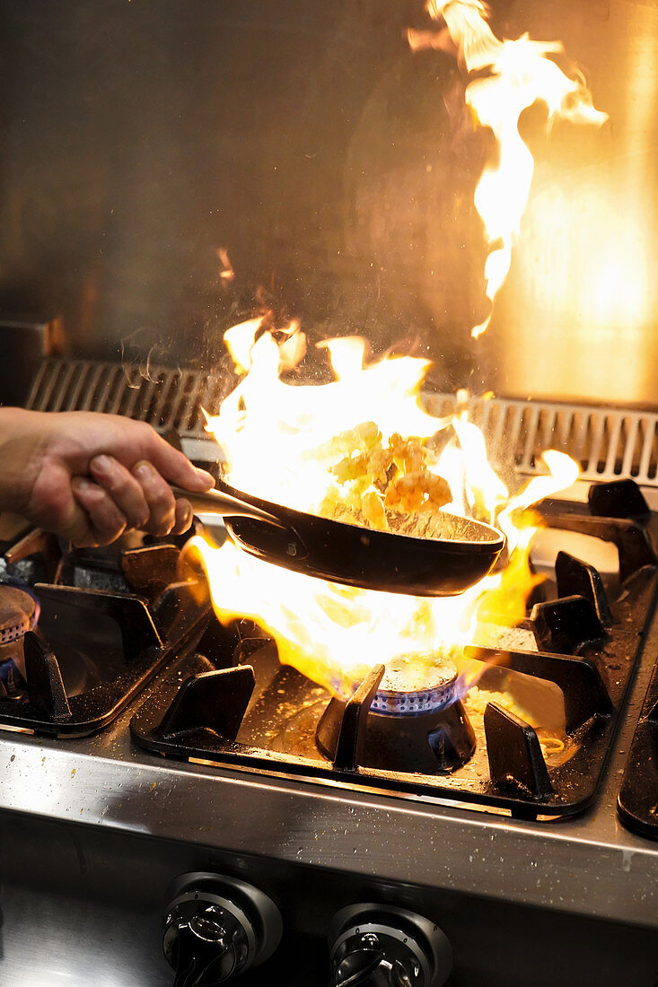 Chef tossing frying shrimps in flambe above gas stove with burning flame while cooking in restaurant