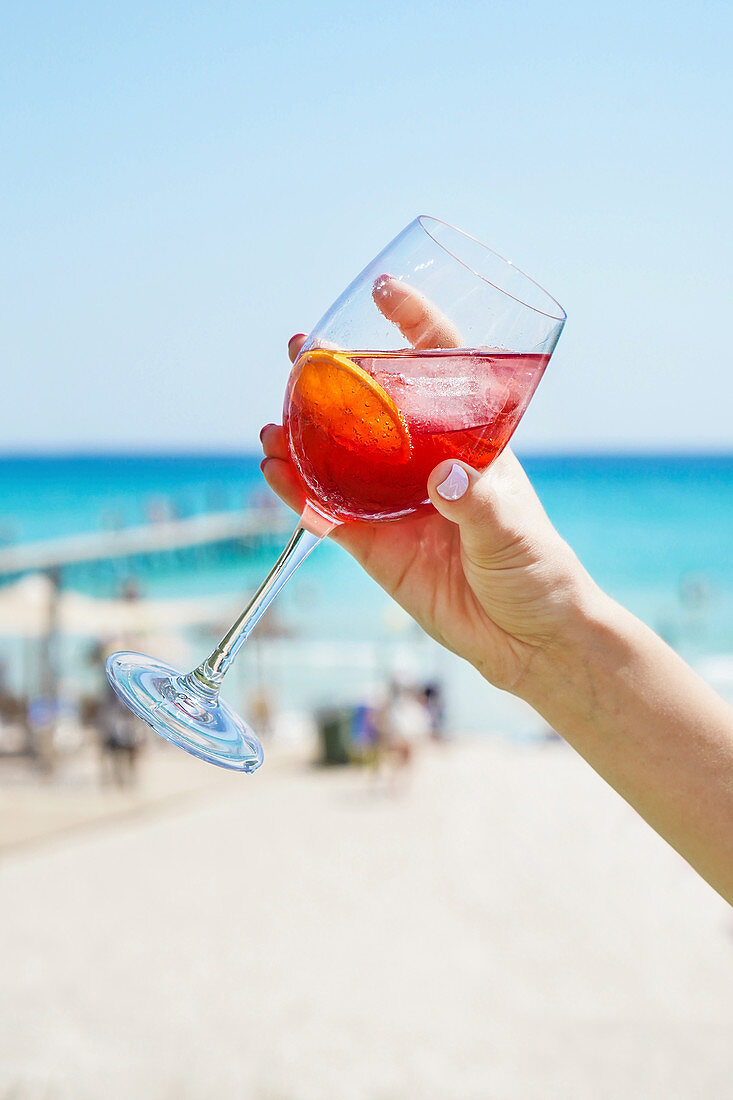 Holding wineglass of refreshing citrus alcoholic cocktail while chilling on sunny beach in summertime