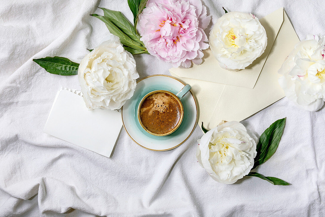 Cup of espresso coffee, blank paper, envelope, pink and white peonies flowers with leaves