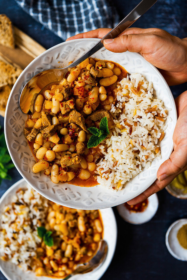 Hands holding a bowl with Turkish white bean stew with lamb and orzo sice pilaf on the side