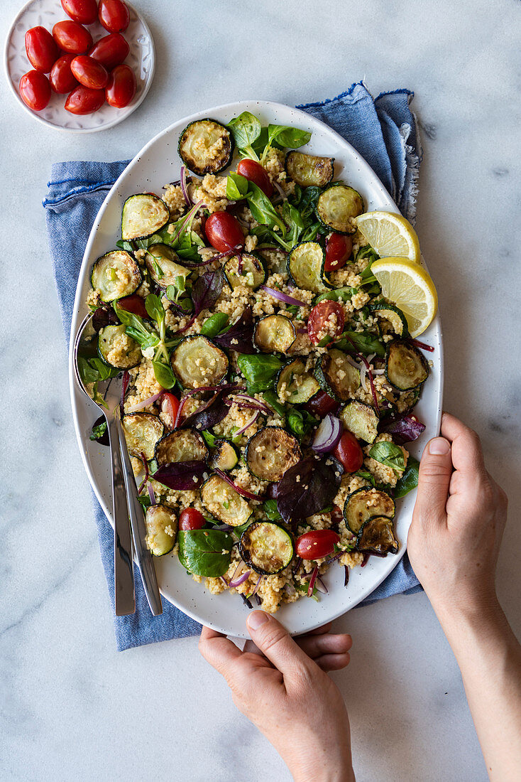 Hands holding zucchini couscous salad with herbs, redd onion and plum tomatoes