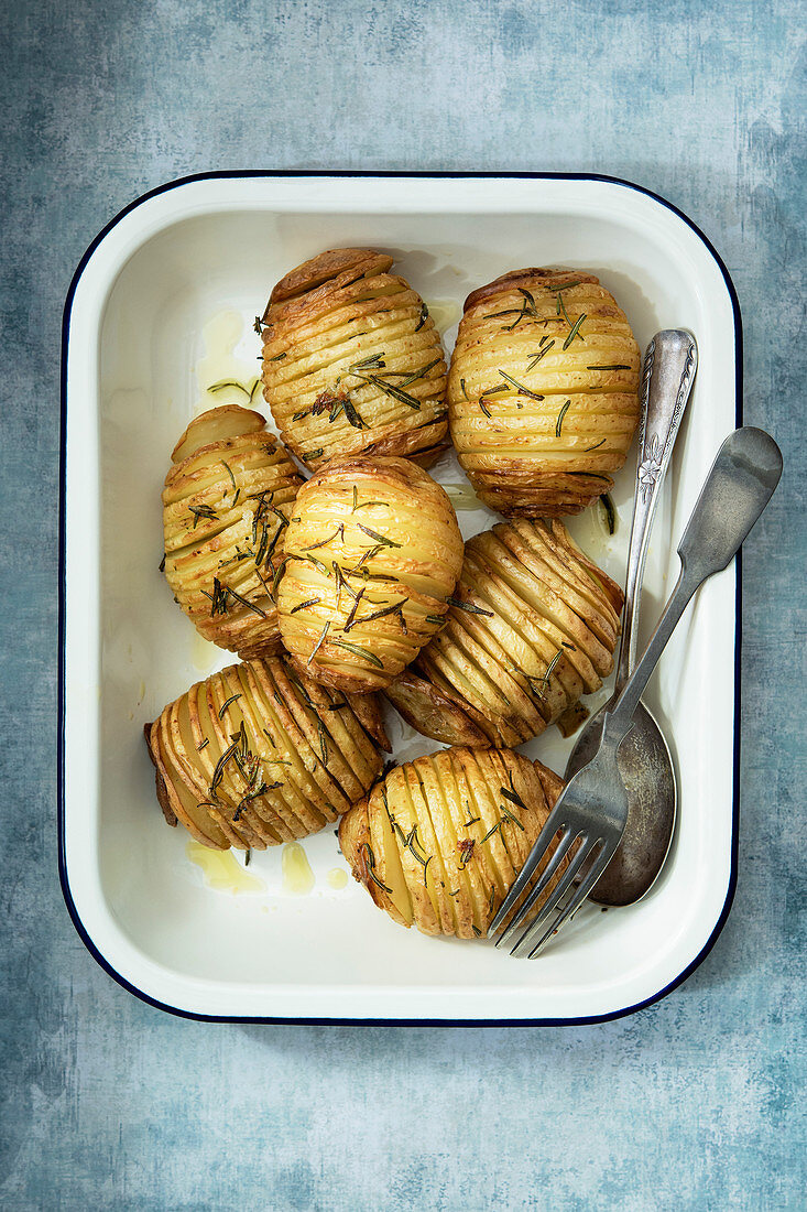 Crispy roasted hasselback potatoes in a serving dish