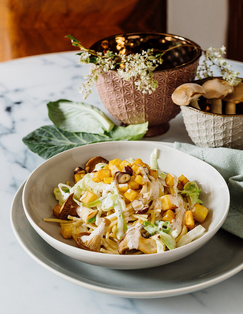 Pointed cabbage and spaghetti in a creamy sauce with diced, baked potatoes