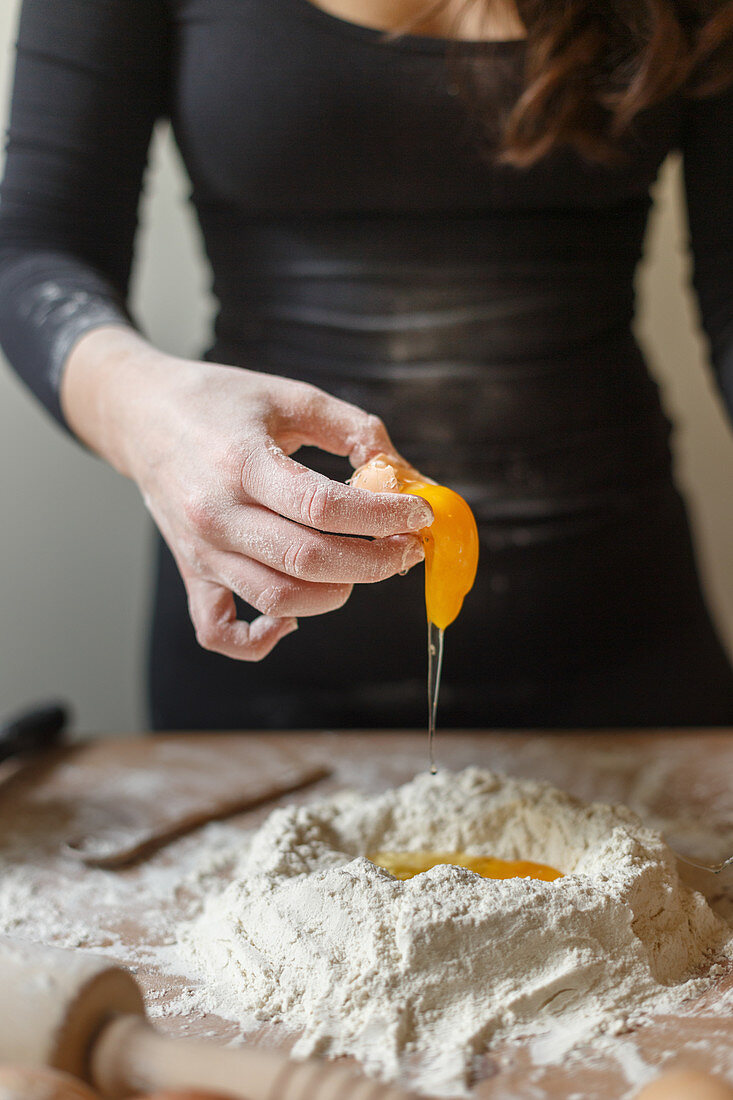 Faceless female in black leather dress breaking raw eggs into flour mass during preparation of pasta dough in kitchen at home in daytime