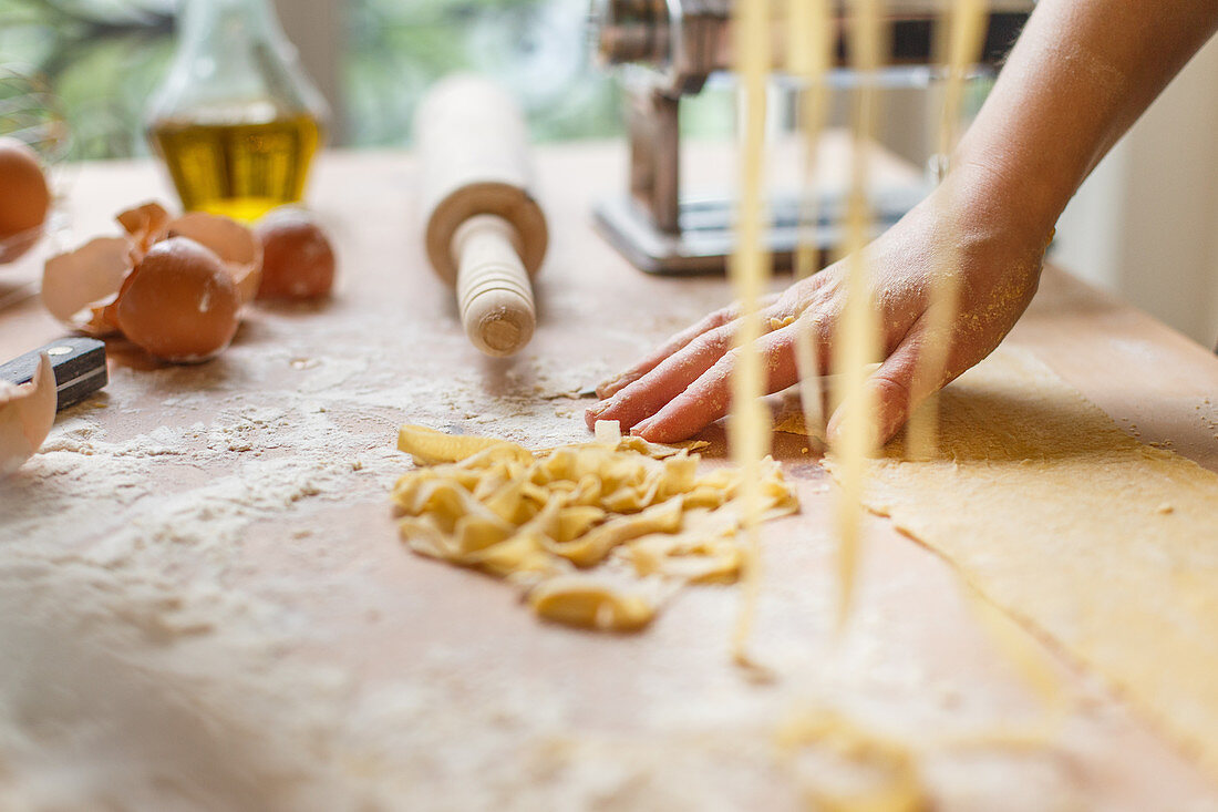 Cutting thin strips of pasta in hands while preparing meal in kitchen