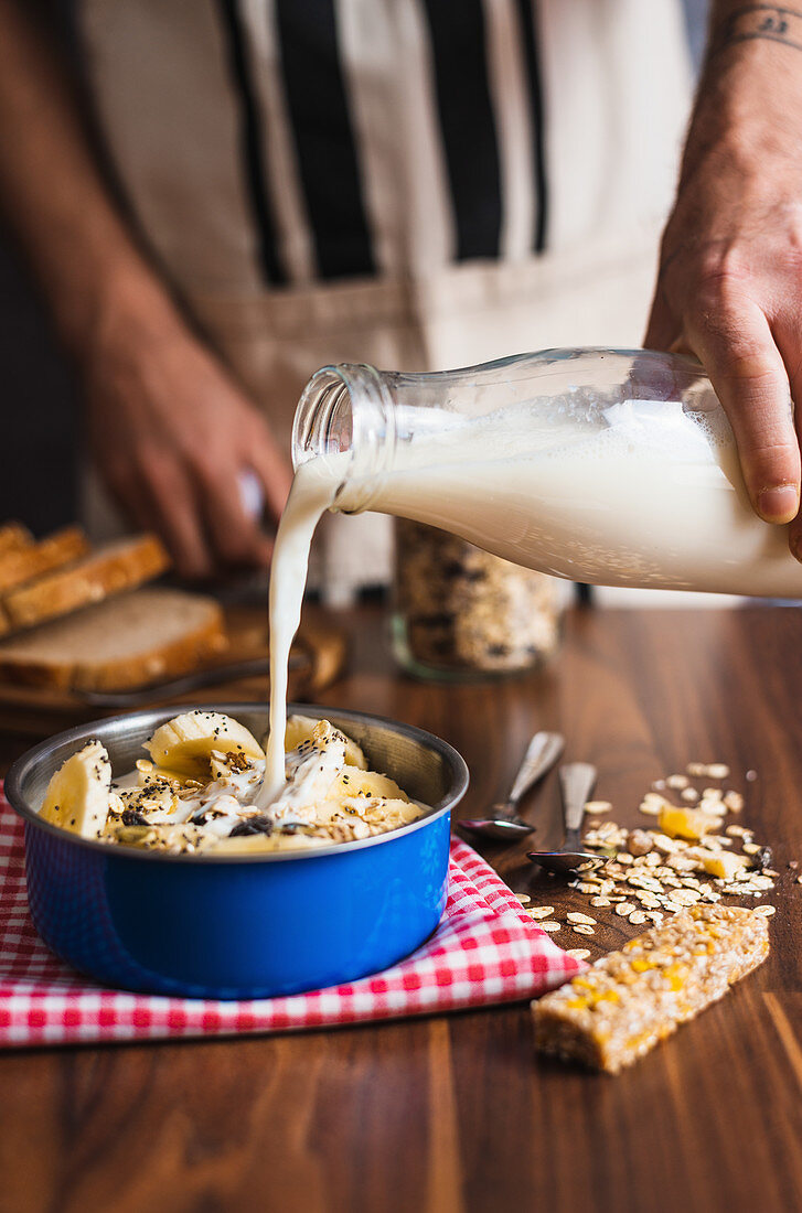 Crop anonymous housewife pouring yogurt from glass bottle into bowl with cereals and banana while preparing healthy breakfast at home kitchen