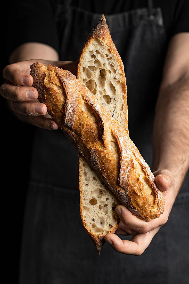 Unrecognizable crop male cook in apron with tasty crunchy baguette in bakery