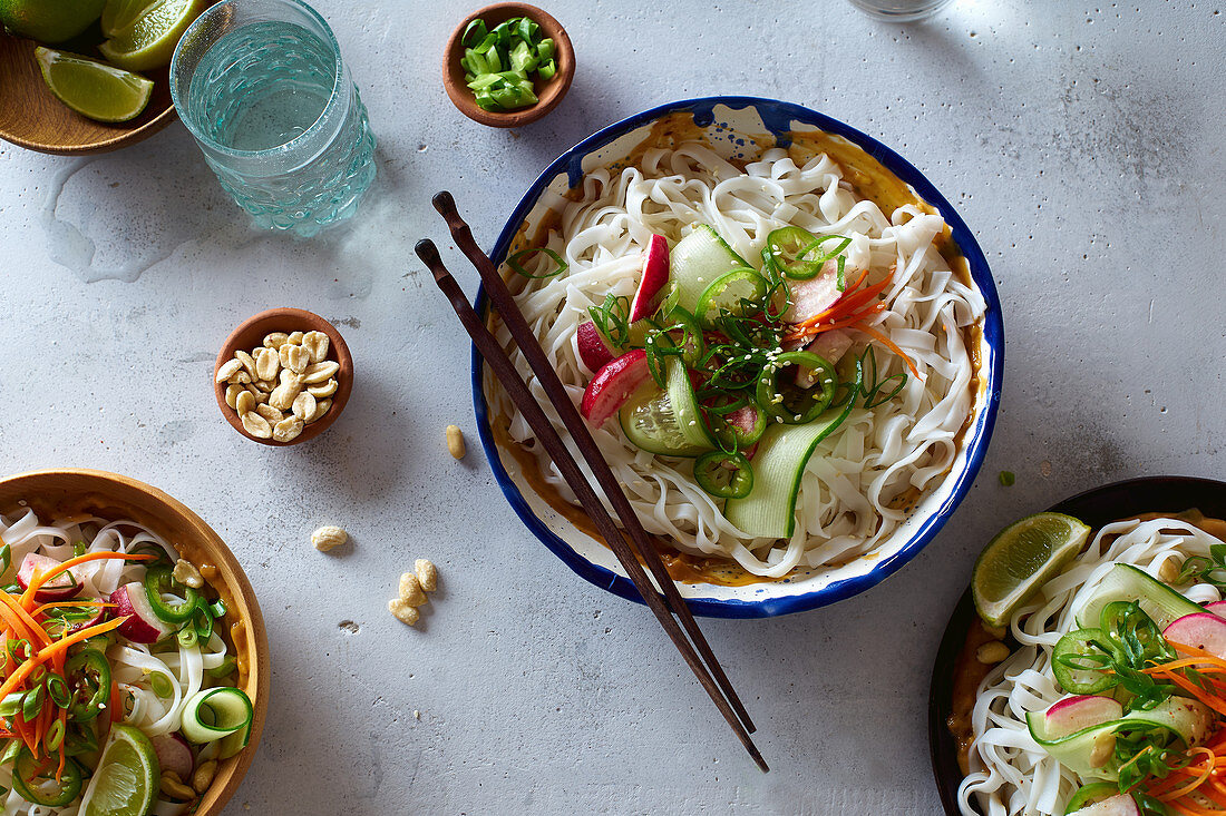 Top view of vegan rice noodle salad made with fresh vegetables, lime and peanut sauce
