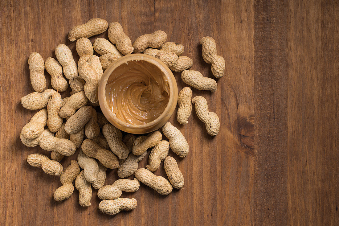 Jar full of peanut butter placed on wooden table in kitchen with peanuts