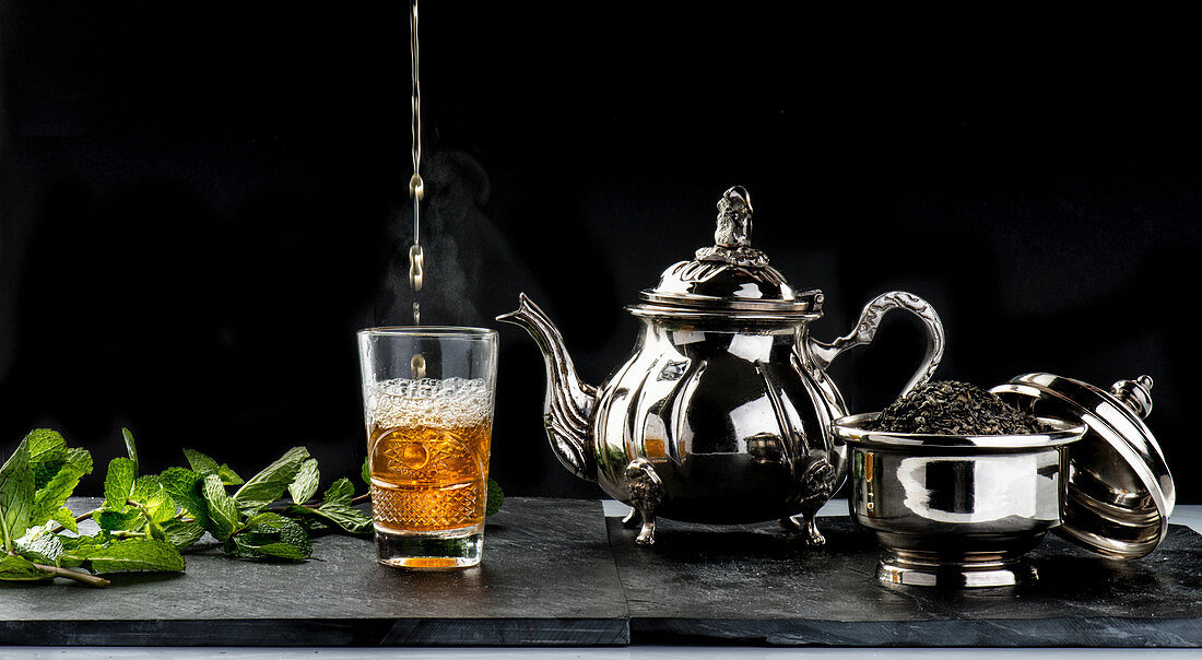 Fresh hot aromatic mint tea being poured into glass cup placed on table