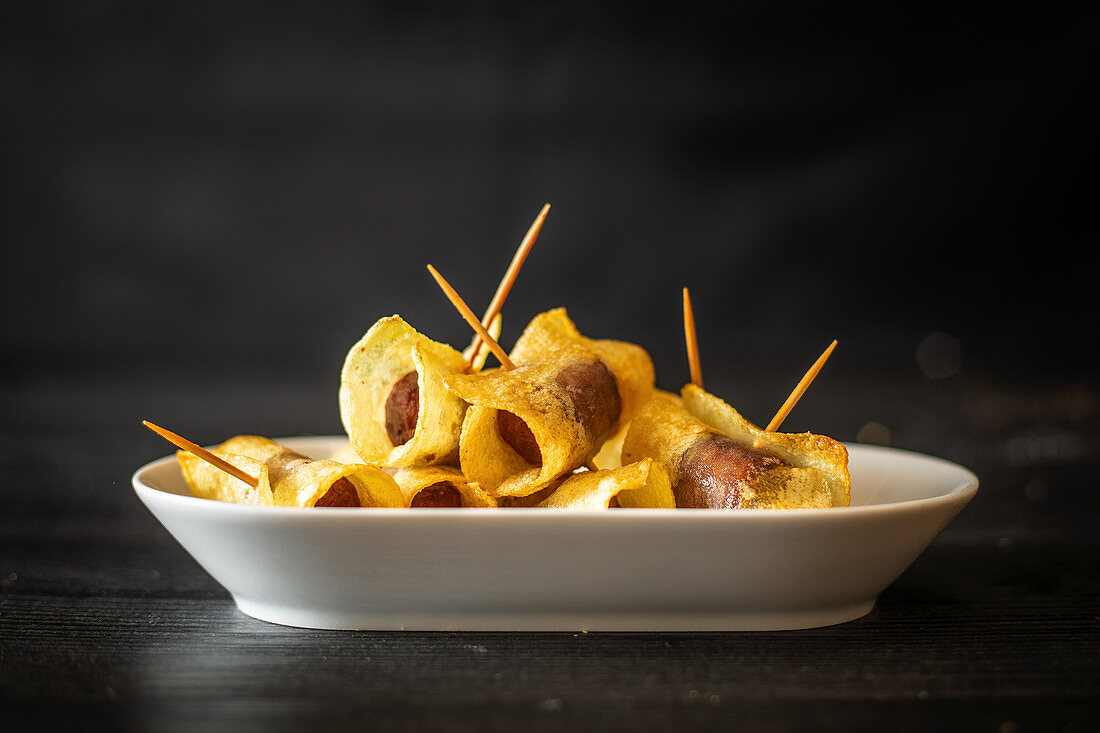 Sausages wrapped in fried potato chips with toothpick and placed on plate on black background