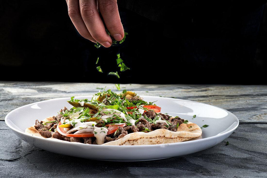 Hawarma with marinated and roasted beef strips and tahini sauce, adding parsley