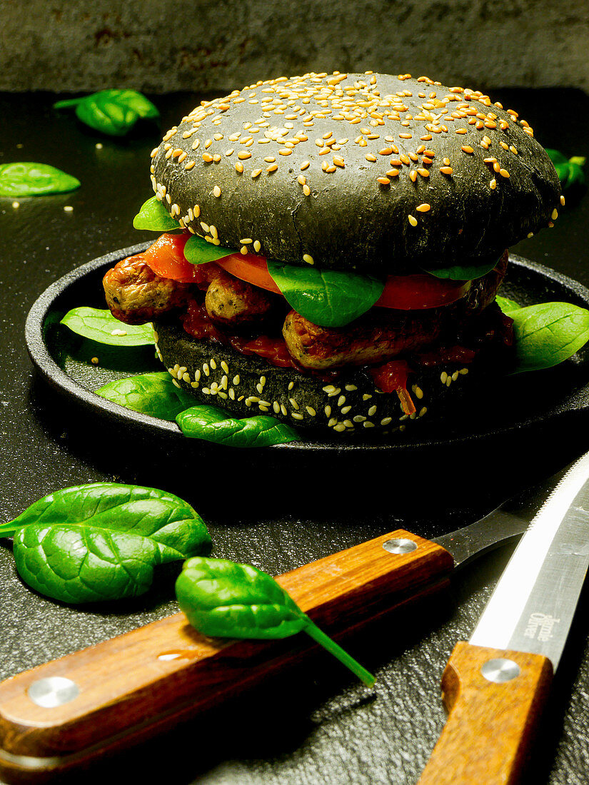 A black burger bun with Nuremberg sausages, spinach, ketchup and tomatoes