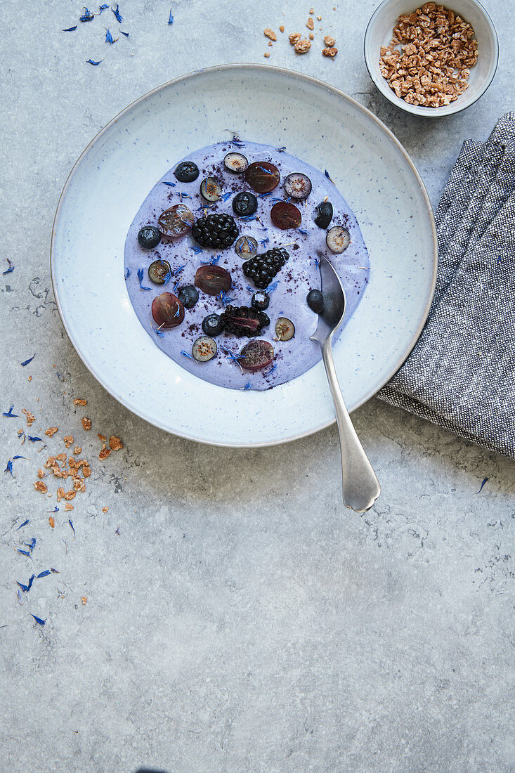 Blue matcha coconut bowl with fresh berries and oat granola