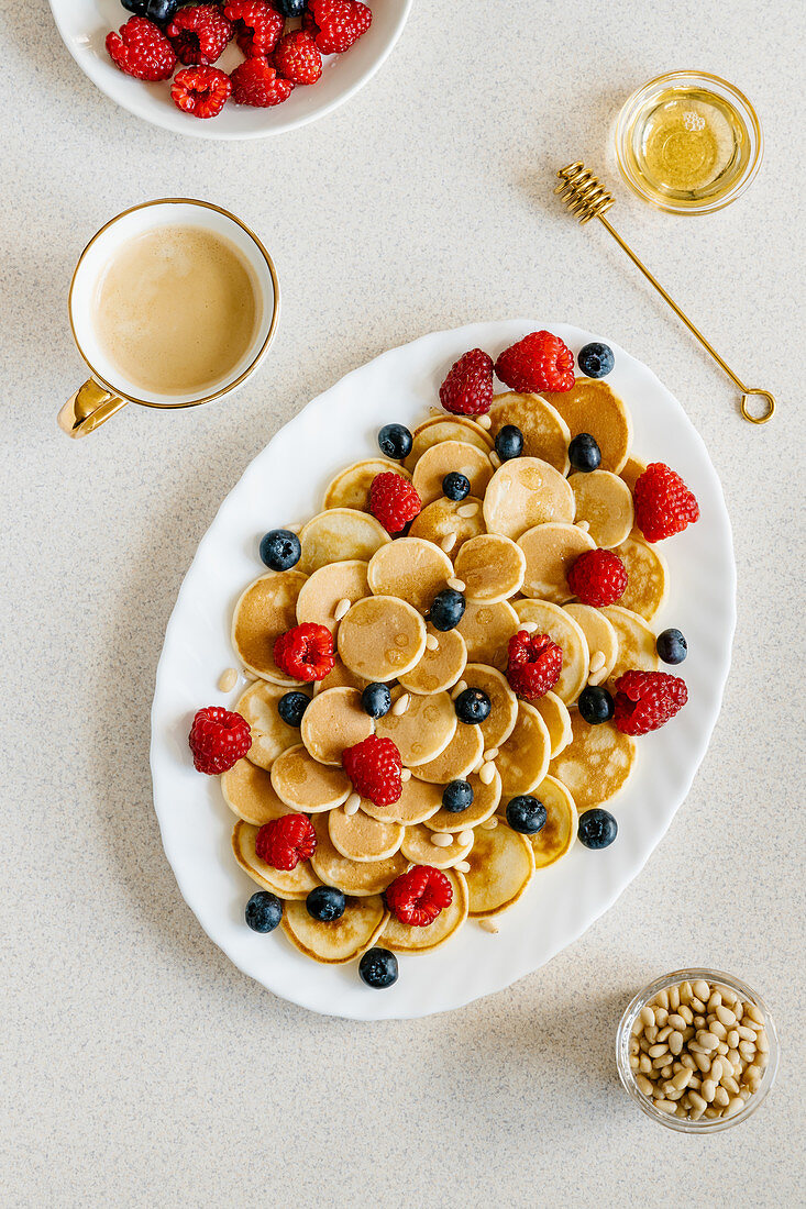 Mini pancakes arranged with berries, pine nuts and agave syrup
