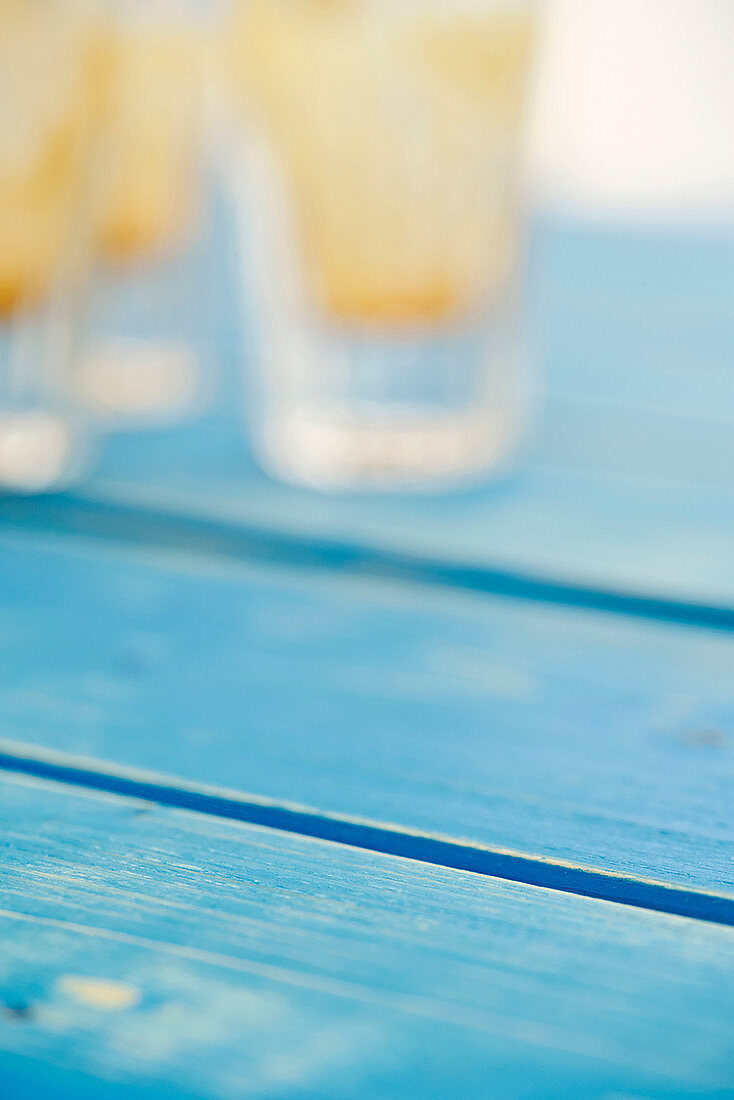 Blue wooden background, empty glasses in the background