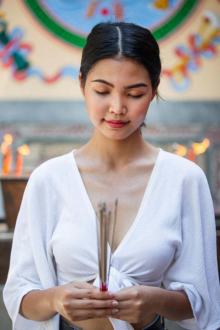 Young Asian woman in front of a Buddhist temple holding incense sticks (Bangkok, Thailand)