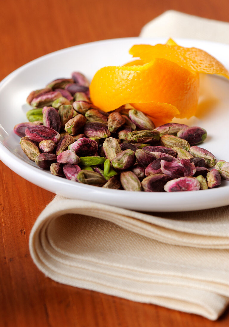 Peeled pistachios on a white plate with orange peel