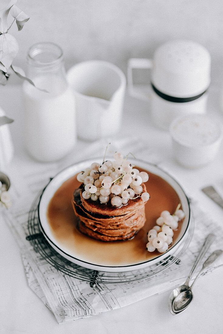 Pumpkin pancakes with white currants topped with maple syrup