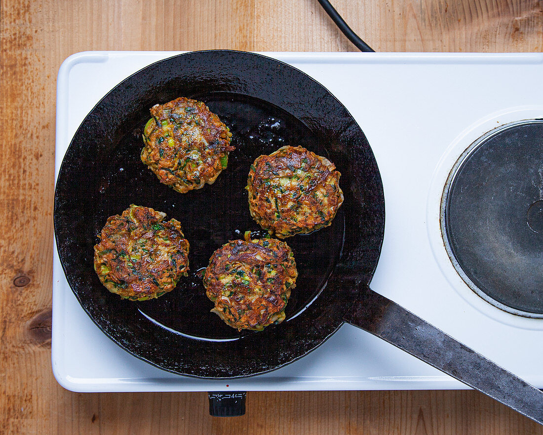 Frying zucchini and leek fritters in a pan
