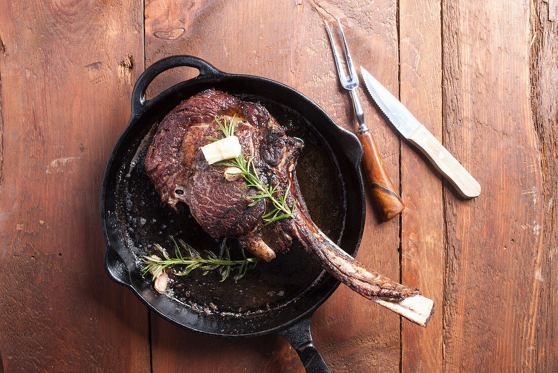 Tomahawk steak in cast iron pan, seasoned with butter and rosemary