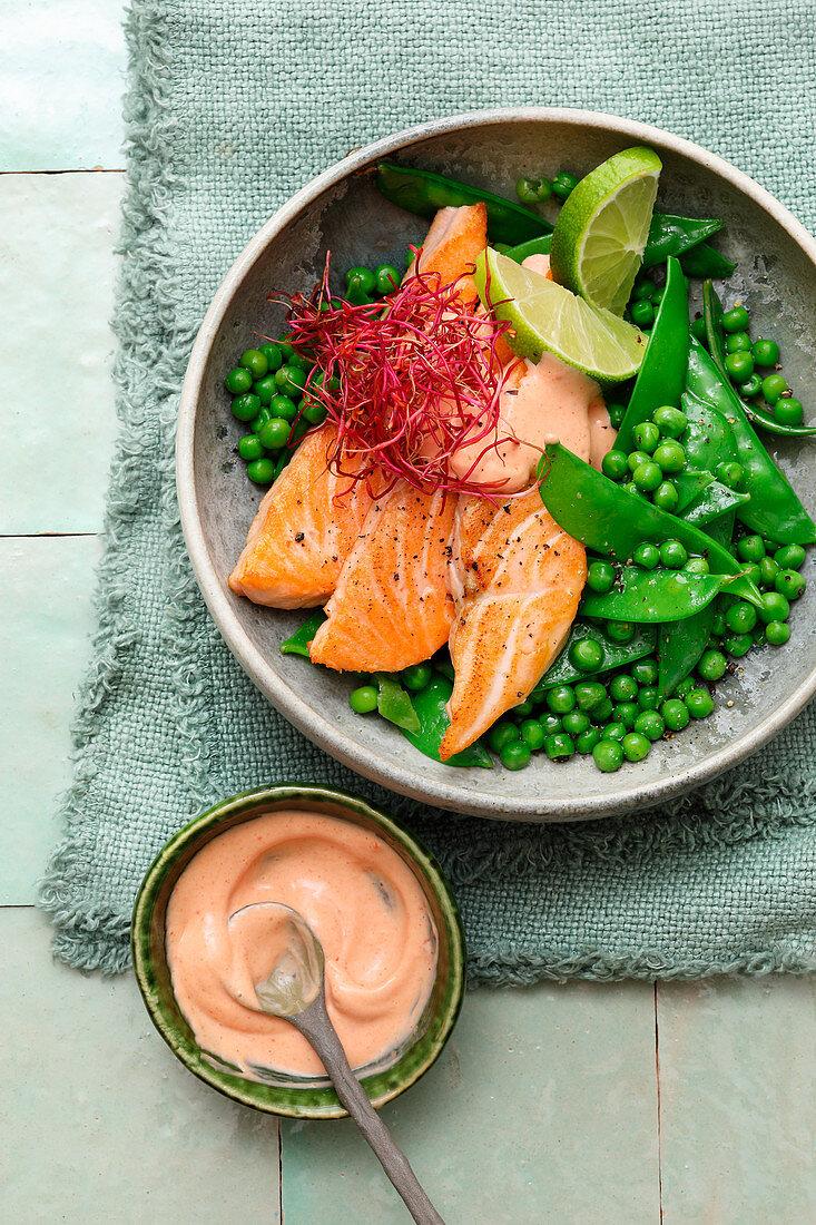 Bowl with sugar snap peas and pea salad and salmon