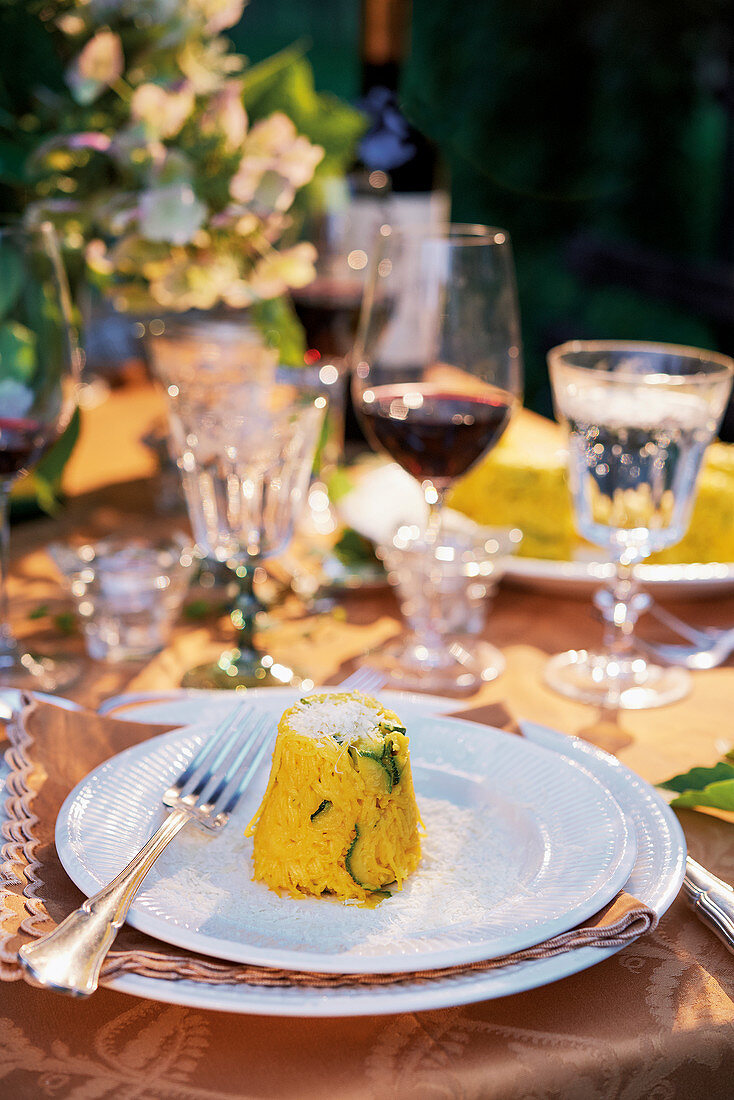 Mini rice timbale with courgette and saffron on a laid table (Italy)