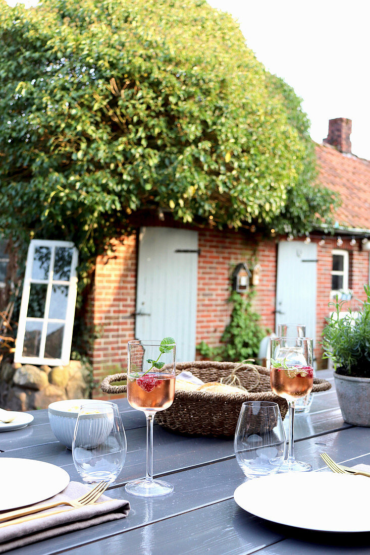 Set table in summery garden of old brick house